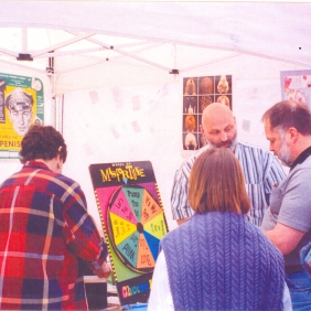 Frank Chaffee and unidentified visitors at AIDS Prevention Project booth at Seattle Pride Fest, ca. 1989/1990. [Series 1825, History files, Seattle-King County Department of Public Health: Prevention Division / HIV-AIDS Program. 1825-10-5.]